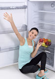 Woman take red apple from fridge Stock Photos