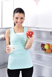 Woman take red apple and milk from fridge Stock Images