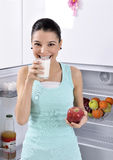 Woman take red apple and milk from fridge Royalty Free Stock Images