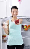 Woman take red apple and milk from fridge Stock Photo