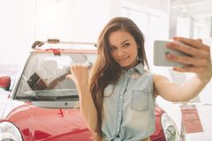 Woman take selfie in a new car at showroom. royalty free stock photos