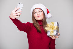 Woman take selfie on phone  with Christmas hat hold gift Stock Photo