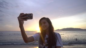 Woman take selfie on smartphone in front of sunrise over the ocean. Woman take selfie on smartphone in front of beautiful sunrise over the ocean stock footage