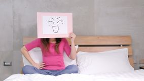 Woman take smile board. On the bed Royalty Free Stock Photography