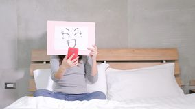 Woman take smile board. And selfie on the bed Royalty Free Stock Images