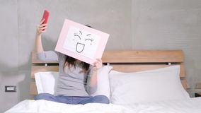 Woman take smile board. And selfie on the bed Stock Photography