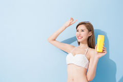 Woman take sunscreen. On the blue background Stock Photography