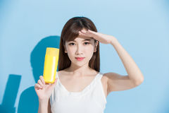Woman take sunscreen. And look somewhere on blue background Stock Photos