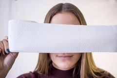 Woman take toilet paper. covers the face.  Royalty Free Stock Photos
