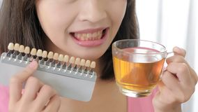 Woman take tooth color palette. And tea with whiten concept stock photo