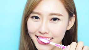 Woman take toothbrush. And smile happily on blue background Stock Photo
