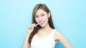 Woman take toothbrush. And smile happily on blue background Stock Images