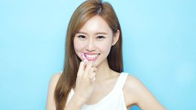 Woman take toothbrush. And smile happily on blue background Royalty Free Stock Image