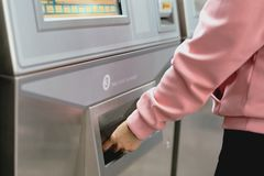 Woman take a train ticket after buy from subway ticket machine. Transportation concept royalty free stock images