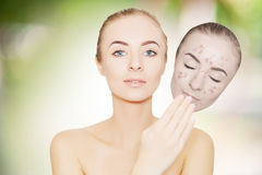 Woman takes away mask with acne and pimples,green outdoor backgr Royalty Free Stock Image