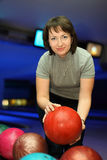 Woman takes ball for playing in bowling Stock Photography