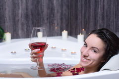 Woman Takes Bath. Beautiful woman in bath with rose petals drinking wine Stock Photography