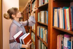 Woman takes book from shelf in university library. Young woman takes book from shelf in university library. Female person in knowledge depository stock photo
