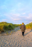 Woman Takes Calm Relaxed Walk Along Beach Stock Images