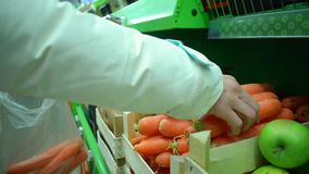 Woman takes a carrot from the shelf in the market, hd video stock footage