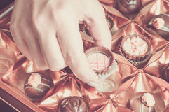 Woman takes a chocolate from the box. Pastel tone Royalty Free Stock Photo