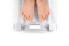 Woman takes her weight with feet Royalty Free Stock Photo