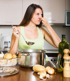 Woman takes lid off pan and feel musty smell Royalty Free Stock Photos