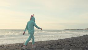 Woman takes a lonely walk on the beach. Lovely woman is taking a stroll across the beach in the evening. She is wearing bright unicorn kigurumi and white stock video footage