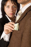 A woman takes a money. Out of a man's pocket. Focus on the money Stock Images