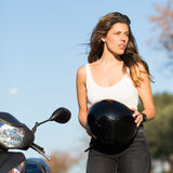 Woman takes off helmet on scooter Stock Photo