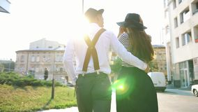 Woman takes off her hat walking with a man along the street on the sunset stock footage