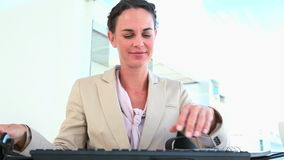 Woman takes off her headset and types on a keyboard Royalty Free Stock Photo
