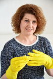 Woman takes off rubber gloves after cleaning Stock Photos