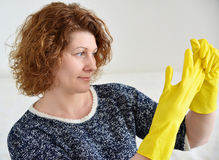 Woman takes off rubber gloves after cleaning Royalty Free Stock Image