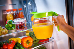Woman takes the Orange juice from the open refrigerator Royalty Free Stock Image