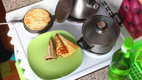 A woman takes out a ready-made cake from the waffle iron. He puts the dough into the waffle iron and closes it. A woman takes out a ready-made cake from the stock footage