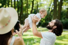 Woman takes a photo of her handsome husband holding in the arms their little charming daughter on a sunny day in the royalty free stock photos