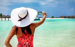 Woman takes a photo of a Maldivian beach setting Stock Images