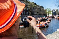 Woman takes photo of party - Koninginnedag 2012 Royalty Free Stock Photography