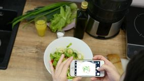 Woman takes photo on smart phone and puts in frame leaves of green salad and cucumber with red tomato stock footage