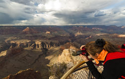 Woman takes photograph of Grand Canyon Royalty Free Stock Photos