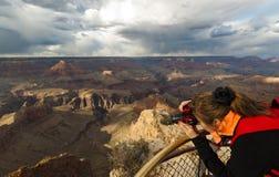 Woman takes photograph of Grand Canyon Royalty Free Stock Photos