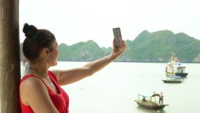 The woman takes the picture against the background of a bay with boats. Taking selfie. Vietnam. The happy woman.The. The woman costs in a bungalow against the stock video