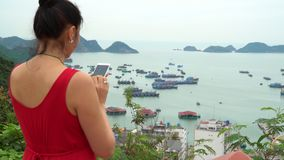 The woman takes the picture of a bay from the top point of the island. The woman costs on a viewing ploshchdka. On this video you can see as the woman holds the stock video
