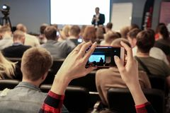 Woman takes a picture during the conference using smartphone stock image