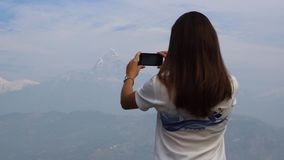 Woman takes a picture of the mountains on a mobile stock footage