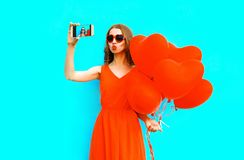Woman takes a picture self portrait on smartphone holds an air balloons Stock Image