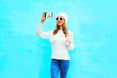 Woman takes a picture self portrait in white knitted sweater, hat on a smartphone. On blue background Royalty Free Stock Photos