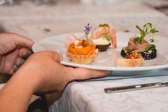Served table for food and wine tasting. Snacks with shrimp, fish fillets, Spain tapas recipe food pintxos. Woman takes plate with snacks with shrimp, fish Stock Photo