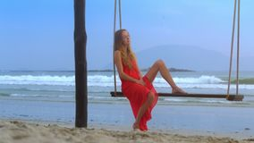 Woman Takes Pleasure in Rest Swinging on Beach Closeup. Closeup beautiful blonde girl in red dress takes pleasure in rest swinging on beach against pictorial stock footage